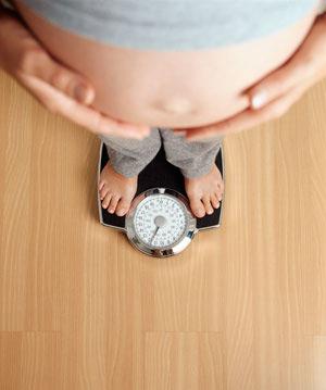 беременная женщина на весах